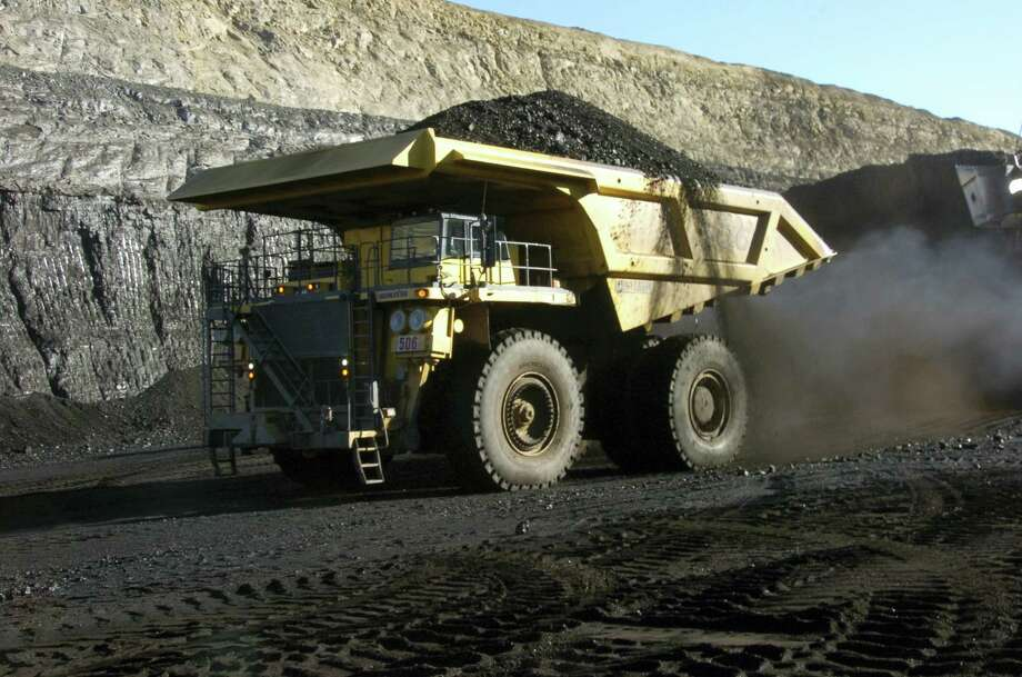 In this Nov. 15, 2016, file photo, a haul truck with a 250-ton capacity carries coal from the Spring Creek strip mine near Decker, Mont. As President Donald Trump touts new oil pipelines and pledges to revive the nation's struggling coal mines, federal scientists are warning that burning fossil fuels is already driving a steep increase in the United States of heat waves, droughts and floods. Photo: AP Photo/Matthew Brown, File  / Copyright 2016 The Associated Press. All rights reserved.