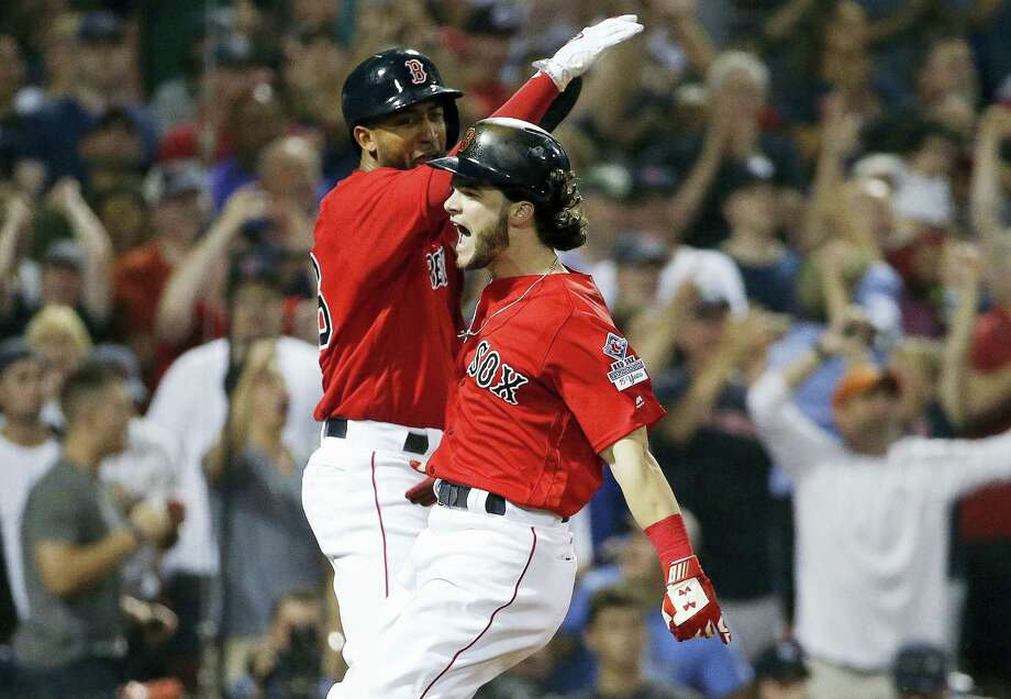Andrew Benintendi, right, and Eduardo Nunez celebrate after scoring in the seventh inning on Friday. Photo: Michael Dwyer — The Associated Press  / AP2017