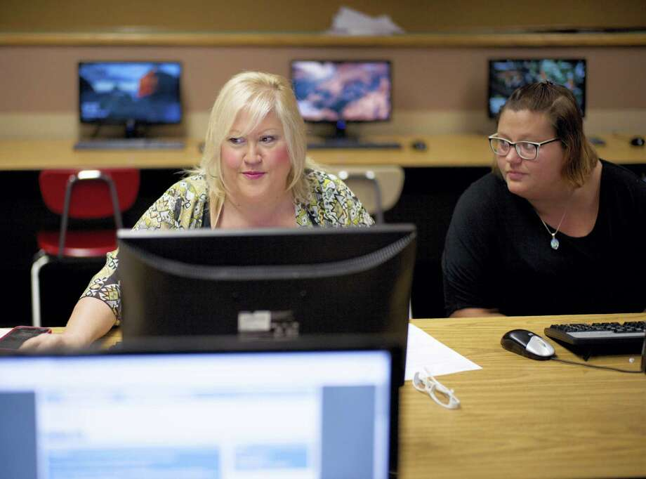 In this Thursday photo, Cheryl Bast, left, is accompanied by her daughter Liz Pierson, as she works on an application for a position with Omaha Public Schools, during a job fair held at Omaha South High School in Omaha, Neb. On Friday the U.S. government issues the July jobs report. Photo: Nati Harnik — The Associated Press  / Copyright 2017 The Associated Press. All rights reserved.