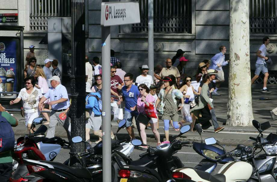 People flee the scene in Barcelona, Spain, Thursday, Aug. 17, 2017 after a white van jumped the sidewalk in the historic Las Ramblas district, crashing into a summer crowd of residents and tourists and injuring several people, police said. Photo: AP Photo/Oriol Duran   / Copyright 2017 The Associated Press. All rights reserved.