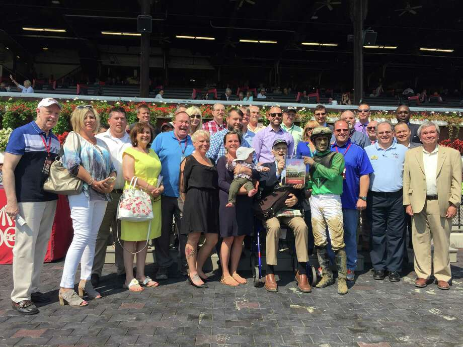 Times Union's Mike Jarboe, a horse racing handicapper for the newspaper, is surrounded by friends and family in the winner's circle after a race named in his honor at Saratoga Race Course on September 4, 2017.