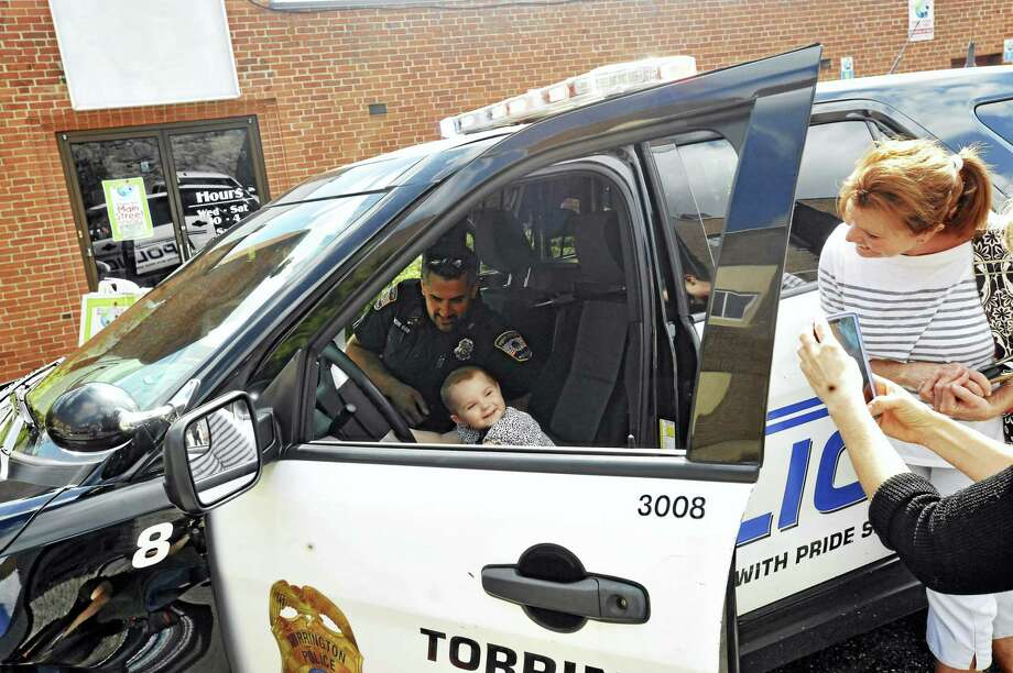 Torrington police officers came to the KidsPlay Children's Museum to meet with children Thursday morning. Outside, Officer Rob Simon shows a child the inside of a police cruiser. Photo: Ben Lambert / Hearst Connecticut Media