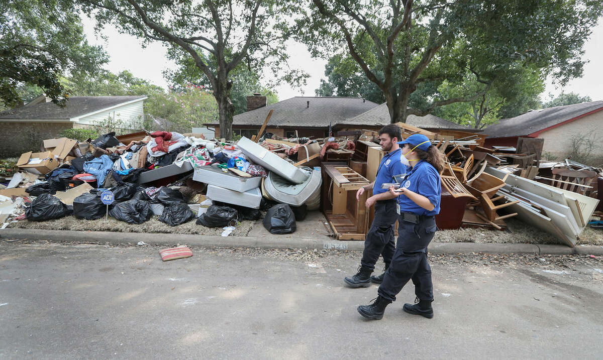 Mary Glenn Krause and Thomas Delano, FEMA Survivor Assistance Team members, go door-to-door connecting with people who need help by signing them up for disaster recovery assistance and answering questions on Friday, Sept. 15, 2017, in Houston. (Steve Gonzales | Houston Chronicle)