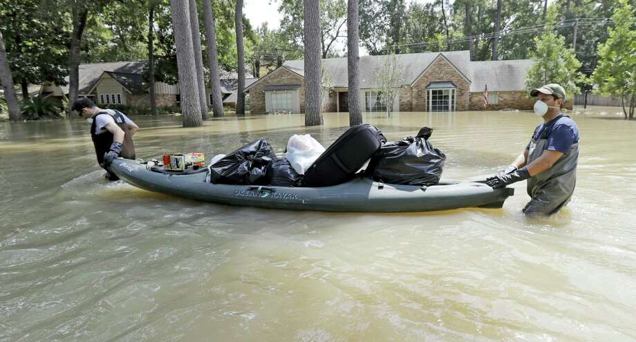 Gaston Kirby, left, is helped by friend Juan Minutella after gathering the last of his belongings from his flooded home in the aftermath of Hurricane Harvey Monday, Sept. 4, 2017, near the Addicks and Barker Reservoirs, in Houston. Photo: AP Photo/David J. Phillip   / Copyright 2017 The Associated Press. All rights reserved.