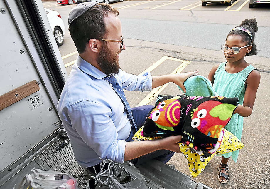 Congregation Beth Israel spiritual leader Rabbi Mendy Hecht accepts a donation from New Haven resident K'niyah Glover, 10, who made three pillows for the Houston flood victims, Thursday, August 31, 2017, at the Amity Shopping Center at 112 Amity Road in New Haven. Members of the Young Jewish Professionals were collecting hygiene products, cleaning supplies and non-perishable food items. (Catherine Avalone/Hearst Connecticut Media) Photo: Hearst Connecticut Media / New Haven Register