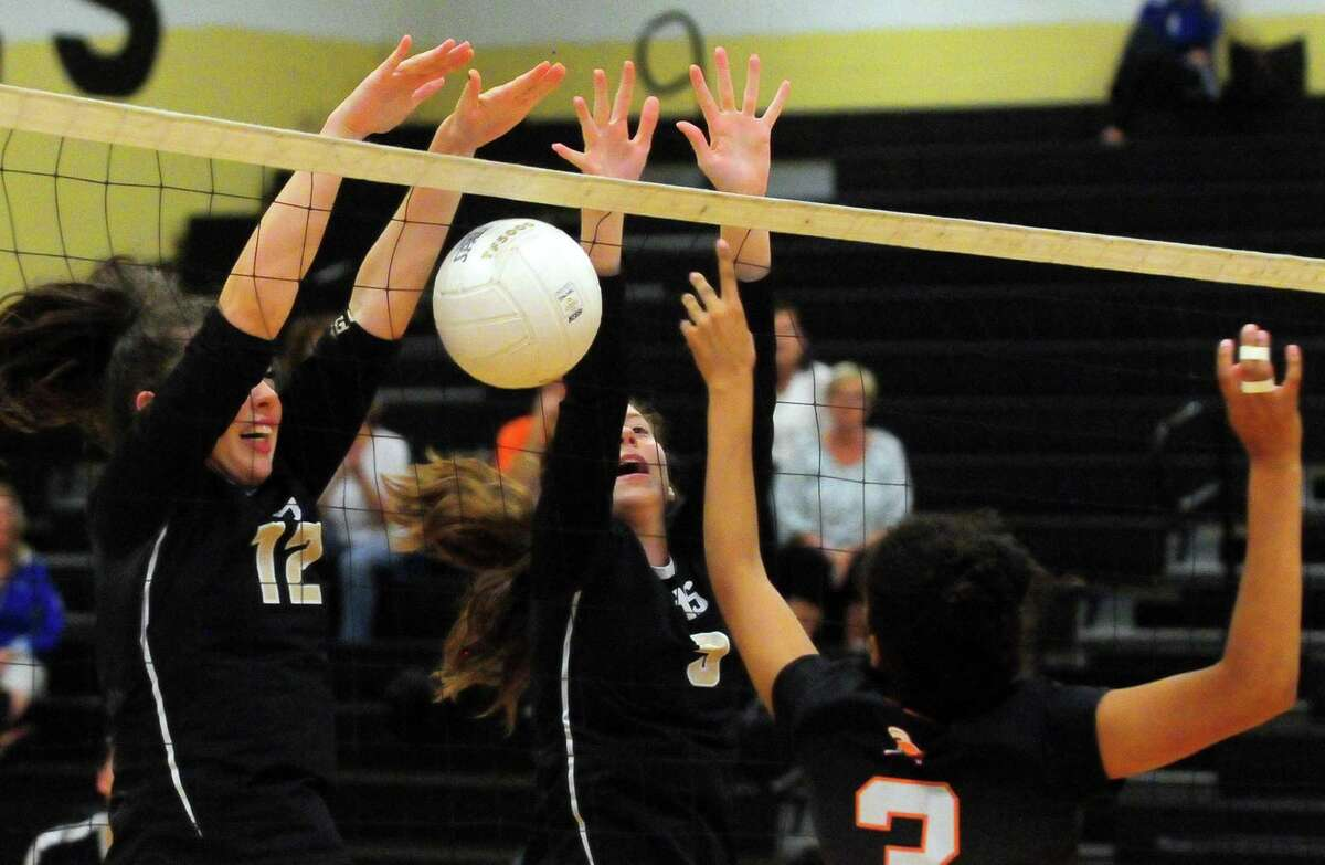 Trumbull's Riley Chase, left, and Julia Roberto, center, deflect a shot by Stamford's Liani Mercado during FCIAC girls volleyball action in Trumbull, Conn. on Tuesday, Sept. 19, 2017.