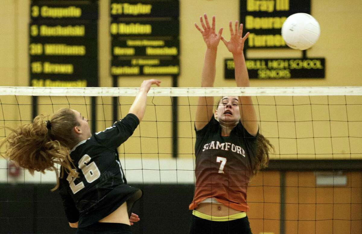 Trumbull's Krystina Schueler, left, spikes the ball past Stamford's Andrea O'Connor during FCIAC girls volleyball action in Trumbull, Conn. on Tuesday, Sept. 19, 2017.