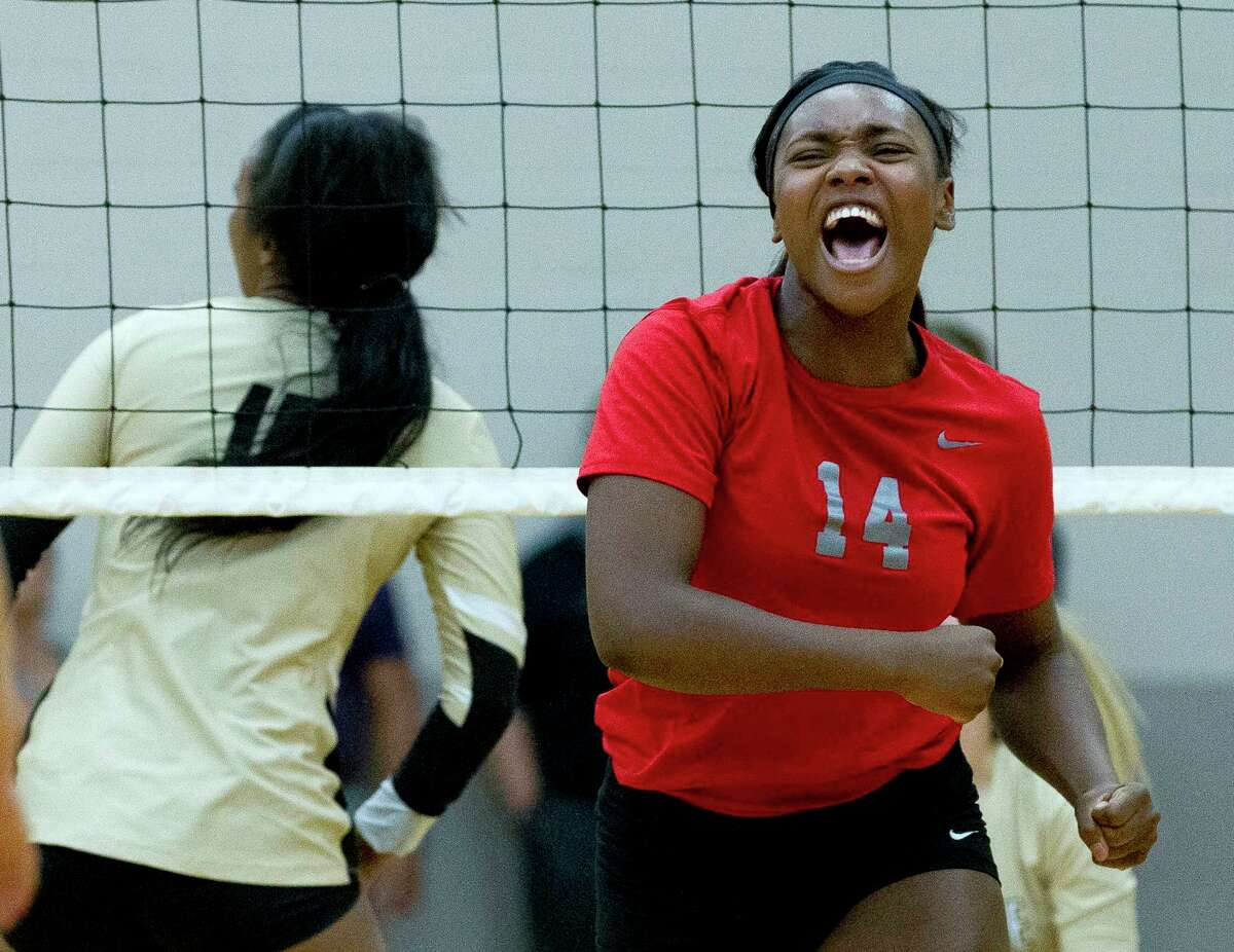 Oak Ridge's Adara Land (14) celebrates scoring a point during the first set of a District 12-6A volleyball match at Conroe High School, Tuesday in Conroe.