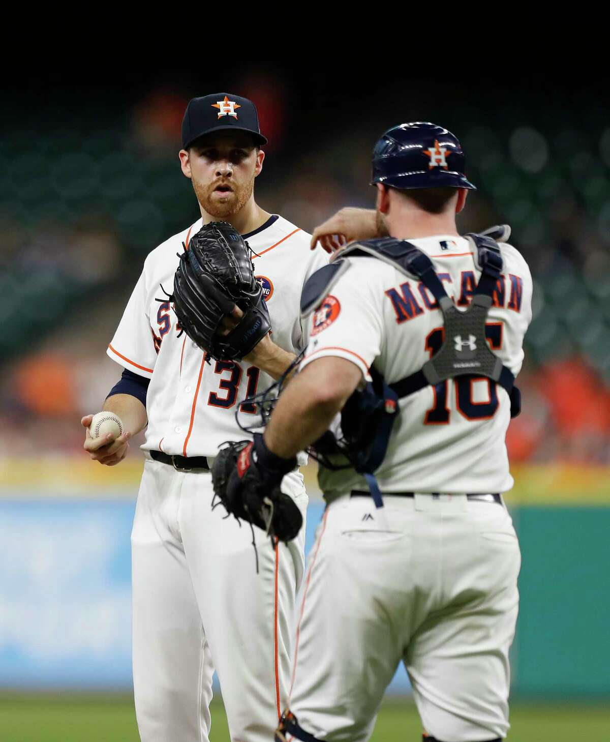 Houston Astros starting pitcher Collin McHugh (31) talks with catcher Brian McCann (16) between batters during the first inning of an MLB baseball game at Minute Maid Park, Tuesday, Sept. 19, 2017, in Houston.