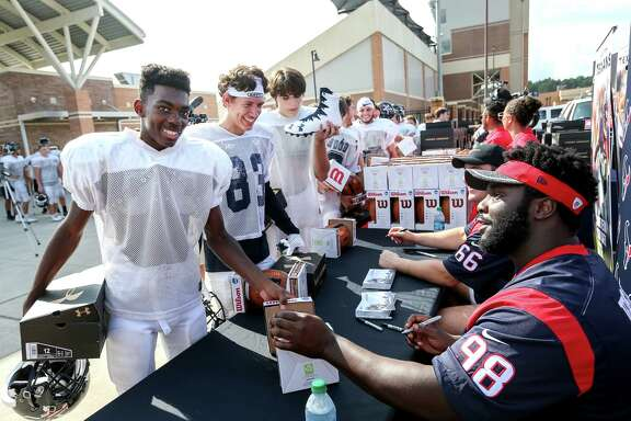 Kingwood High School football players Darrell Edwards, left, and Alex Grifaldo, second from left, joke with Houston Texans nosetackle D. J. Reader (98) as he and center Nick Martin (66) pass out new footballs and shoes, at Turner Stadium, Tuesday, Sept. 19, 2017, in Humble.  ( Jon Shapley  / Houston Chronicle )