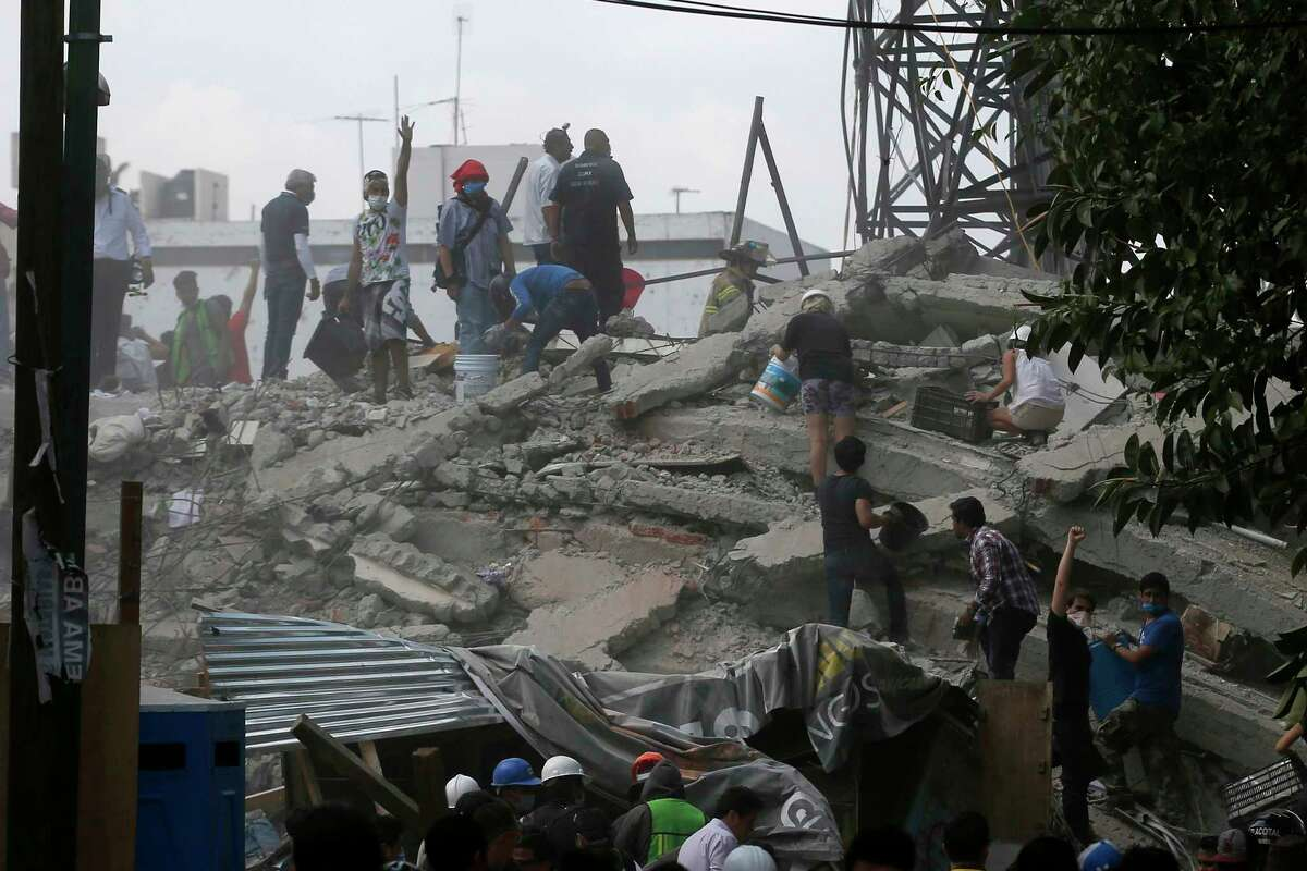 Volunteers search a building that collapsed after an earthquake, in the Roma neighborhood of Mexico City, Tuesday, Sept. 19, 2017. A magnitude 7.1 earthquake has rocked central Mexico, killing at least 55 people as buildings collapsed in plumes of dust and thousands fled into the streets in panic. (AP Photo/Eduardo Verdugo)