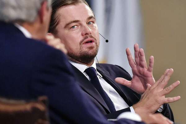 Actor and activist Leonardo DiCaprio talks with former Secretary of State John Kerry at the Yale Climate Conference Tuesday at Woosley Hall in New Haven.