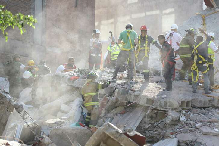 First responders work on removing the rubble of a collapsed building looking for survivors trapped underneath, after a 7.1 earthquake in Mexico City, Tuesday, Sept. 19, 2017.  The earthquake stunned central Mexico, killing more than 100 people as buildings collapsed in plumes of dust.  (AP Photo/Gustavo Martinez Contreras)