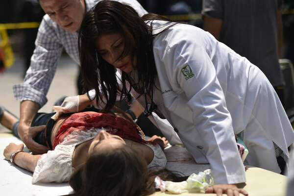 An injured woman is helped after a powerful quake in Mexico City on September 19, 2017. A powerful earthquake shook Mexico City on Tuesday, causing panic among the megalopolis' 20 million inhabitants on the 32nd anniversary of a devastating 1985 quake. The US Geological Survey put the quake's magnitude at 7.1 while Mexico's Seismological Institute said it measured 6.8 on its scale. The institute said the quake's epicenter was seven kilometers west of Chiautla de Tapia, in the neighboring state of Puebla.  / AFP PHOTO / Pedro Pardo        (Photo credit should read PEDRO PARDO/AFP/Getty Images)