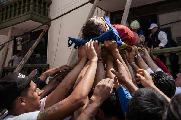 MEXICO CITY, MEXICO - SEPTEMBER 19: Rescuers and residents assist an injured victim amid the ruins of a building knocked down by a magnitude 7.1 earthquake that jolted central Mexico damaging buildings, knocking out power and causing alarm throughout the capital on September 19, 2017 in Mexico City, Mexico. The earthquake comes 32 years after a magnitude-8.0 earthquake hit on September 19, 1985. (Photo by Pedro Mera/Getty Images)