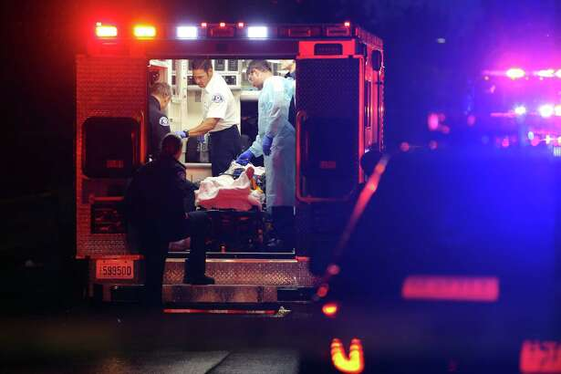 Paramedics attend to the victim of a fatal shooting in West Seattle in the 8100 block of 31st Avenue SW, Tuesday, Sept. 19, 2017 around 7:30 p.m. The victim was pronounced dead at the scene, police are searching for the shooter who may have fled in a car.