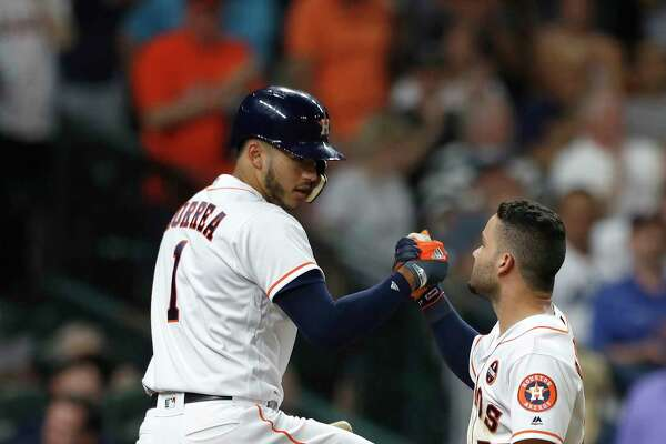 Teammate Carlos Correa, left, almost seems happier about Jose Altuve's game-tying home run in the fourth inning than the second baseman, who also Tuesday was named winner of the Lou Gehrig Memorial Award.