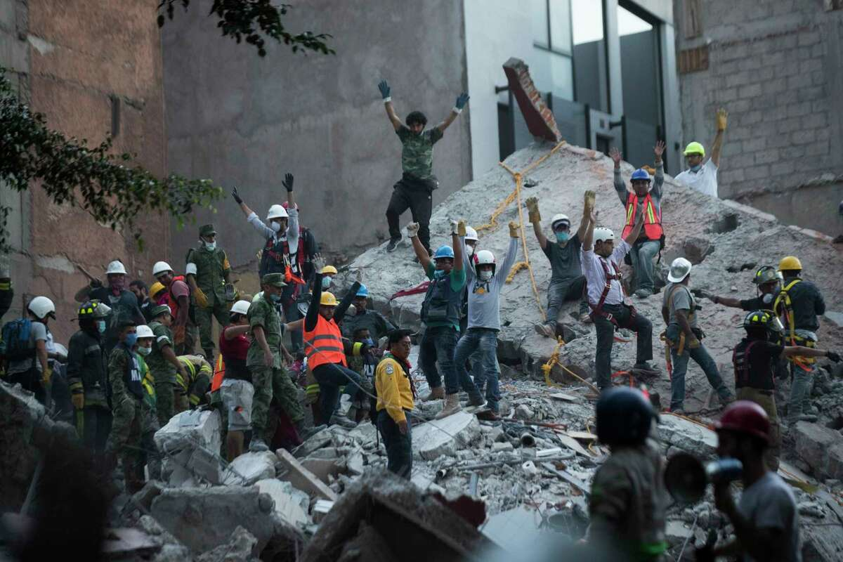 Rescuers ask the volunteers to raise the hands and keep silence as a way to be able to communicate, organize and also listen to possible victims inside the rubble, Tuesday, Sept. 19, 2017, in Mexico City.