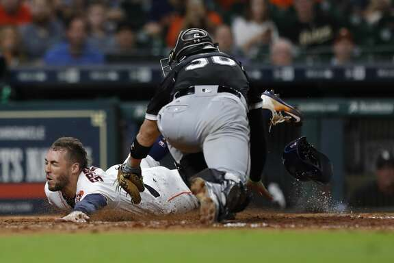 Houston Astros George Springer (4) dives home as he scored a run on  Jose Altuve's ground out during the eighth inning of an MLB baseball game at Minute Maid Park, Tuesday, Sept. 19, 2017, in Houston.  ( Karen Warren / Houston Chronicle )