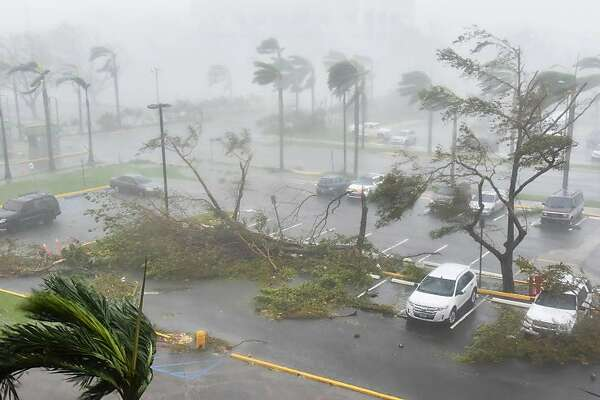 "Trees are toppled in a parking lot at Roberto Clemente Coliseum in San Juan, Puerto Rico, on September 20, 2017, during the passage of the Hurricane Maria. Maria made landfall on Puerto Rico on Wednesday, pummeling the US territory after already killing at least two people on its passage through the Caribbean. The US National Hurricane Center warned of ""large and destructive waves"" as Maria came ashore near Yabucoa on the southeast coast. / AFP PHOTO / HECTOR RETAMALHECTOR RETAMAL/AFP/Getty Images"