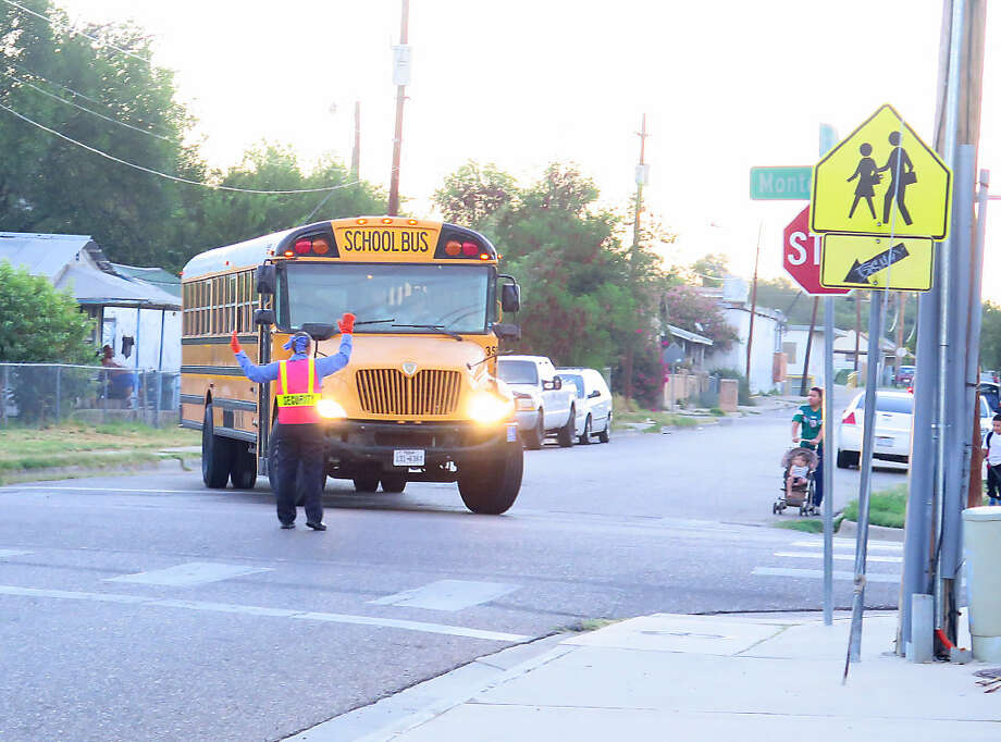 A crossing guard directs a school bus as a family prepares to cross the street for the first day of classes at J.C. Martin Elementary, Monday, August 21, 2017. Photo: Cuate Santos/Laredo Morning Times