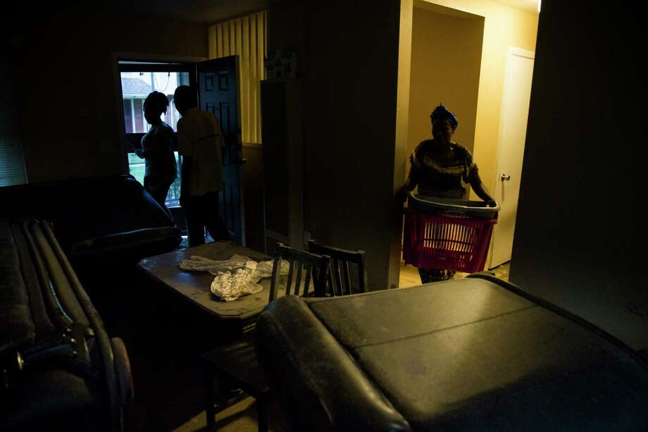 From left, Olivia Izabayo, 14, and her parents, Damien Munyamariza and Marie Nyiraburanga move belongings out of their former apartment at Clayton Homes Tuesday, Sept. 19, 2017 where they and other residents who were flooded during Hurricane Harvey were told that they must pay rent for apartments that were unlivable or lose their subsidies for public housing. Photo: Michael Ciaglo, Houston Chronicle / Michael Ciaglo