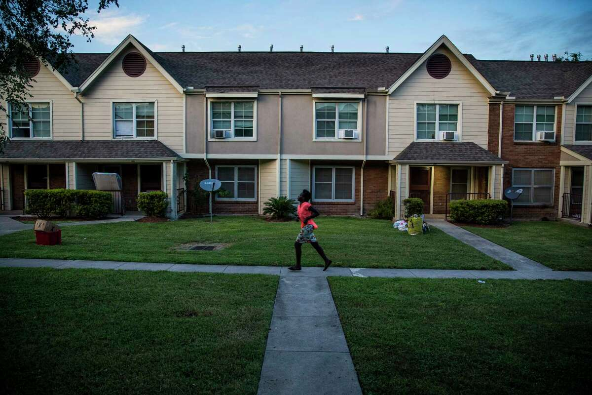 A girl runs in-between buildings at Clayton Homes Tuesday, Sept. 19, 2017 where residents who were displaced by Hurricane Harvey were told they must pay rent for apartments that were unlivable or lose their subsidies for public housing.