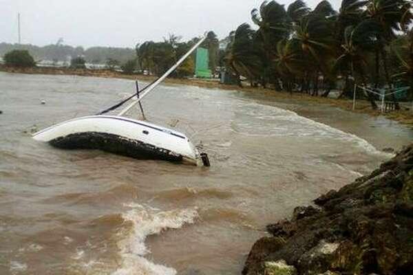 Un boote está volcado en la costa de Sainte-Anne, en la isla caribeña francesa de Guadalupe, martes 19 de septiembre de 2017, poco después del paso del huracán María. (AP Foto/Dominique Chomereau-Lamotte)