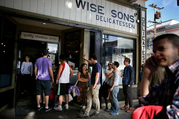 People waiting in line at  Wise Son's Jewish Delicatessen  trails outside the front doors and along the front of the restaurant as Brian Yolles (right),  of Pacifica, talks to a friend on the phone about their reservation for five at Wise Son's Jewish Delicatessen on Saturday, October 25, 2014 in San Francisco, Calif.  Yolles had a reservation but was uncertain about waiting as the line was so long.