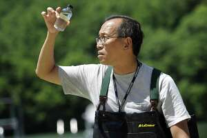 Edwin Wong, a biology professor at Western Connecticut State University, takes a sample of water from the beach at Lynn Demning Park in New Milford.