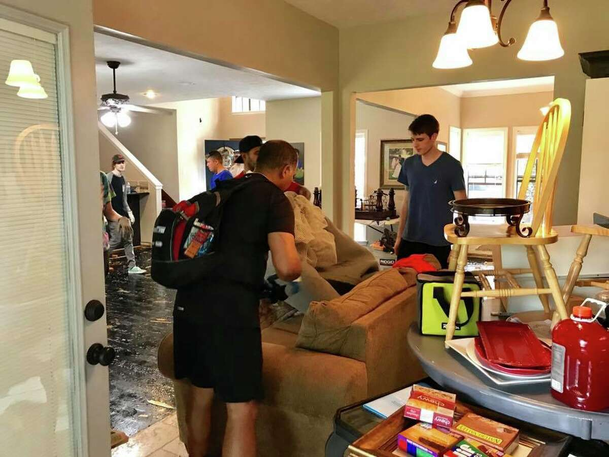 Members of the Rotary Club of Katy work on cleaning up the home of Chris Garcia after it was damaged by Hurricane Harvey flooding.