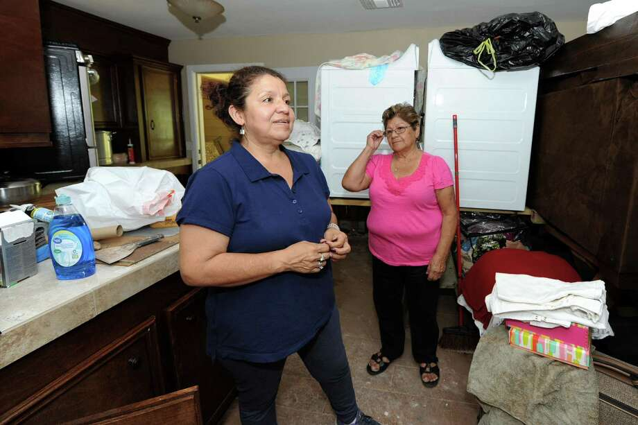 Laura Rendon describes the damage her family's homes sustained the Tinsley Estates area near the Brazos River in Rosenberg, TX as her mother, Angelina Arguello looks over her shoulder on September 7, 2017. Photo: Craig Moseley, Staff / ©2017 Houston Chronicle