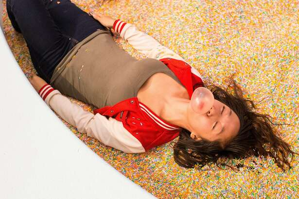 Holly Vo blows a bubble while posing for a friend's photo in the Sprinkle Pool at the Museum of Ice Cream in San Francisco, Calif., on Sunday, September 17, 2017. The pop-up exhibit opened in San Francisco on Sunday.