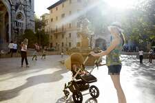 Stock image of a young mother with baby stroller in city.