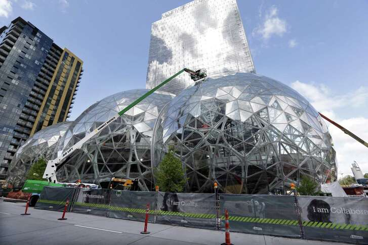 """In this April 27, 2017 file photo, construction continues on three large, glass-covered domes as part of an expansion of the Amazon.com campus in downtown Seattle. Amazon said Thursday, Sept. 7, that it will spend more than $5 billion to build another headquarters in North America to house as many as 50,000 employees. It plans to stay in its sprawling Seattle headquarters and the new space will be """"a full equal"""" of its current home, said founder and CEO Jeff Bezos."""