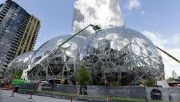 "In this April 27, 2017 file photo, construction continues on three large, glass-covered domes as part of an expansion of the Amazon.com campus in downtown Seattle. Amazon said Thursday, Sept. 7, that it will spend more than $5 billion to build another headquarters in North America to house as many as 50,000 employees. It plans to stay in its sprawling Seattle headquarters and the new space will be ""a full equal"" of its current home, said founder and CEO Jeff Bezos."