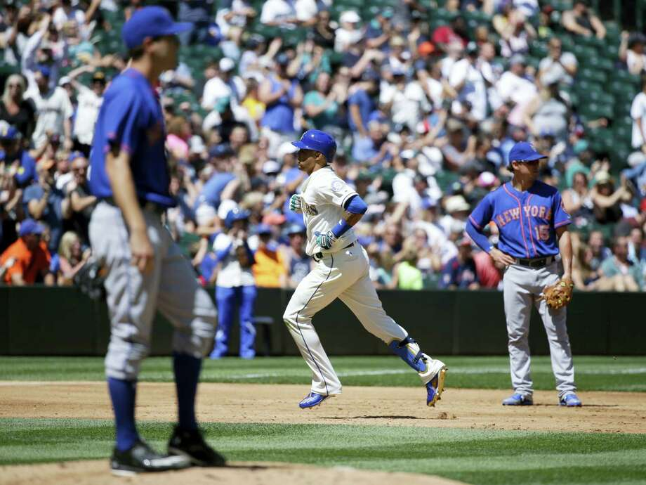 The Mariners' Leonys Martin, center, rounds the bases as Mets starting pitcher Seth Lugo looks on on Sunday. Photo: Ted S. Warren — The Associated Press  / Copyright 2017 The Associated Press. All rights reserved.