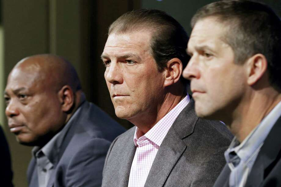 Baltimore Ravens owner Steve Bisciotti, center, listens to a reporter's question as he sits between general manager and executive vice president Ozzie Newsome, left, and head coach John Harbaugh at an NFL football news conference on Feb. 24, 2015 in Owings Mills, Md. Photo: AP Photo – Patrick Semansky  / AP