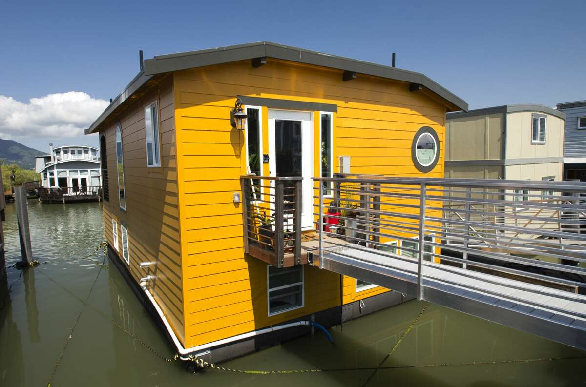 """Dock A 1C """"Shanti Ghar"""" (Peaceful Home):1,280 square feet, two stories Backstory: For over fifteen years, the barge for this floating home was moored next to the owners' old houseboat in the Co-op waiting for the Waldo Point Harbor renovation project to create 38 new slips, one of which would be theirs. With the aid of architect Robert Hayes, the couple designed a home with every feature they wanted in less than 600 square feet. When finally built, the home was floated here to one of the four slips created this year. Owners:Michael Labate and Catherine Lyons"""