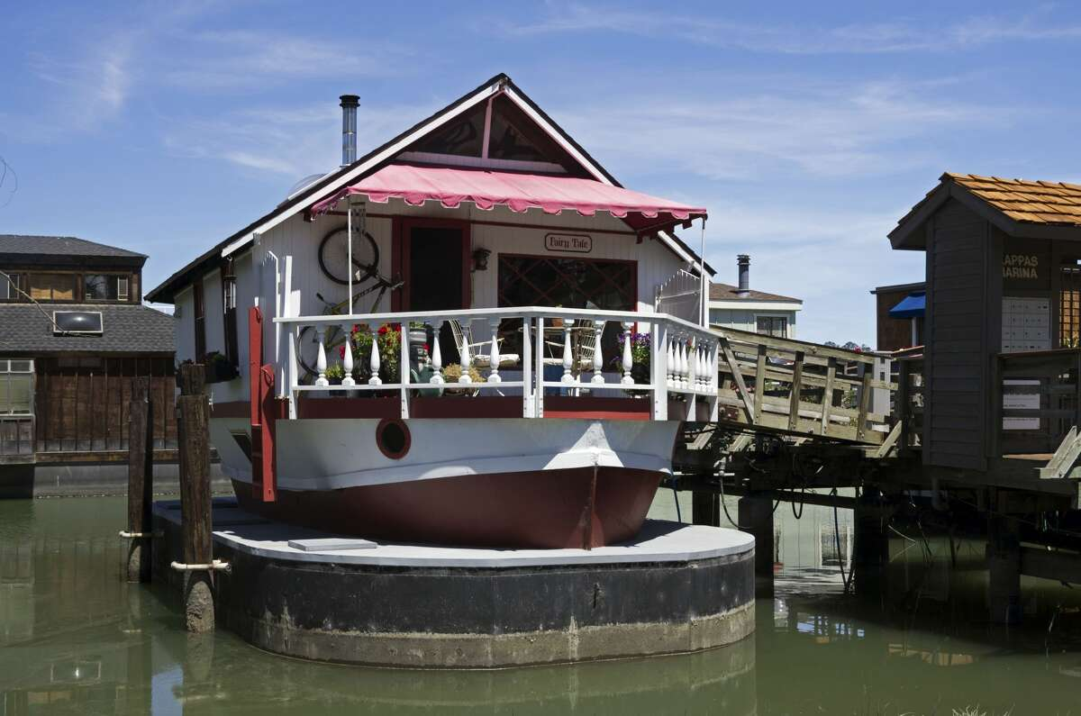 """2 West Pier """"Fairy Tale"""": 1,000 square feet and two stories Backstory: The hull of a 35-foot lifeboat built in 1944 -- just two months before the D-Day invasion -- this charmer was turned into a houseboat in Alameda in 1968 by Ken Gutherson and Ron Muskar. They had purchased it for $200 and put another $2000 into its conversion. Now, sitting atop a ship-shaped concrete barge -- which provides additional storage space -- she is cozy with a warm wooden feel. As you walk aboard on the front deck, notice the profusion of wind chimes. The deck also affords a view of Kappas Marina's lawn area which will be the scene of much activity on tour day. Owners: Julie Durbin and Ed Lopez"""