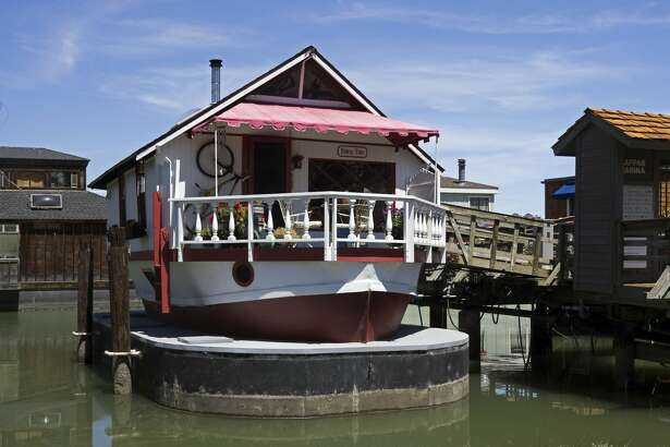 """2 West Pier  """"Fairy Tale""""  Owner: Julie Durbin and Ed Lopez Square Footage: 1,000 / Number of Stories: 2  The hull of a 35-foot lifeboat built in 1944 -- just two months before the D-Day invasion -- this charmer was turned into a houseboat in Alameda in 1968 by Ken Gutherson and Ron Muskar. They had purchased it for $200 and put another $2000 into its conversion. Now, sitting atop a ship-shaped concrete barge -- which provides additional storage space -- she is cozy with a warm wooden feel.  As you walk aboard on the front deck, notice the profusion of wind chimes. The deck also affords a view of Kappas Marina's lawn area which will be the scene of much activity on tour day.  Entering the main floor, you find yourself under bird-pattern stained glass skylights in the wooden beamed ceiling of the living/dining area with its wood burning stove. Notice the masks and frames from Cameroon, El Salvador, Aruba and Guatemala.  In the stern, you will find a compact but fully functional kitchen with open shelving to give it a European flair and windows to bring in water views. The bathroom features a shower with its own skylight. The bathroom walls have been built out to provide storage space in every nook and cranny.  Below decks, the space has been divided in thirds for a bedroom, a den and -- wonder of wonders on a floating home -- a walk-in closet! The art includes paintings by Julie's students from her time living in China and her special education students in Marin. The middle room is both a den and an office, with a television placed to encourage snuggling."""