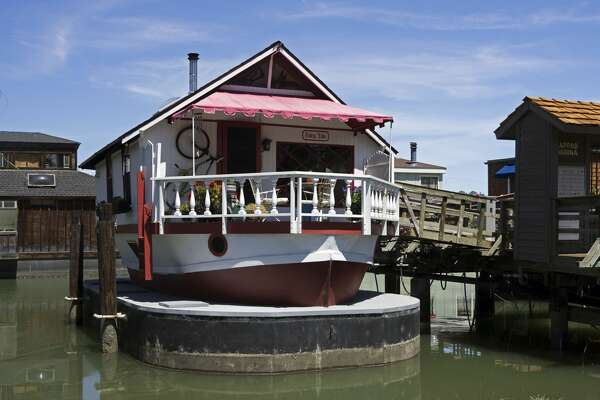 "2 West Pier  ""Fairy Tale""  Owner: Julie Durbin and Ed Lopez Square Footage: 1,000 / Number of Stories: 2  The hull of a 35-foot lifeboat built in 1944 -- just two months before the D-Day invasion -- this charmer was turned into a houseboat in Alameda in 1968 by Ken Gutherson and Ron Muskar. They had purchased it for $200 and put another $2000 into its conversion. Now, sitting atop a ship-shaped concrete barge -- which provides additional storage space -- she is cozy with a warm wooden feel.  As you walk aboard on the front deck, notice the profusion of wind chimes. The deck also affords a view of Kappas Marina's lawn area which will be the scene of much activity on tour day.  Entering the main floor, you find yourself under bird-pattern stained glass skylights in the wooden beamed ceiling of the living/dining area with its wood burning stove. Notice the masks and frames from Cameroon, El Salvador, Aruba and Guatemala.  In the stern, you will find a compact but fully functional kitchen with open shelving to give it a European flair and windows to bring in water views. The bathroom features a shower with its own skylight. The bathroom walls have been built out to provide storage space in every nook and cranny.  Below decks, the space has been divided in thirds for a bedroom, a den and -- wonder of wonders on a floating home -- a walk-in closet! The art includes paintings by Julie's students from her time living in China and her special education students in Marin. The middle room is both a den and an office, with a television placed to encourage snuggling."