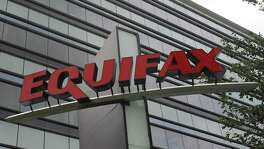 This Saturday, July 21, 2012, photo shows signage at the corporate headquarters of Equifax Inc. in Atlanta. With lawyers collecting as much as a third of any payout from a class action settlement, the company may end up spending an average of less than $1 per person for credit monitoring and out-of-pocket expenses for 143 million Equifax consumers whose data was compromised. of 143 million Americans. (AP Photo/Mike Stewart)
