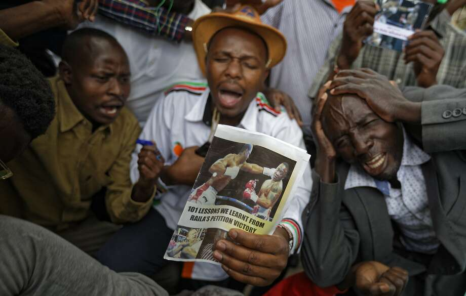 Supporters of Raila Odinga hold up a paper depicting him (left) knocking out the president. Photo: Ben Curtis, Associated Press