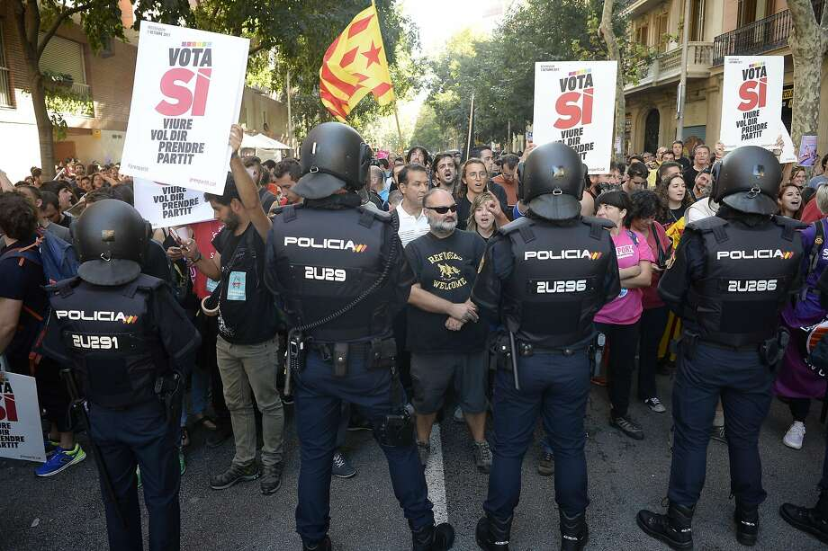 National police officers stand in front of pro-referendum demonstrators during a protest in Barcelona. Photo: JOSEP LAGO, AFP/Getty Images