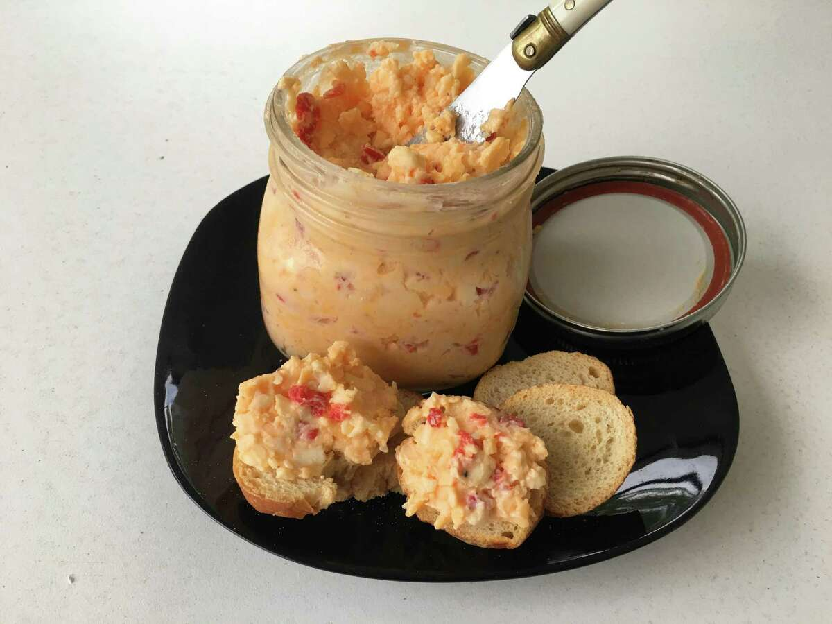 This 2017 photo shows Classic Pimento Cheese from a recipe by Elizabeth Karmel, in Houston, Texas. This comfort food is basically only three simple ingredients, sharp cheddar cheese, jarred pimentos and mayonnaise - but when you combine them, you get a creamy, sharp, piquant spread that is so versatile you can use it for just about any meal part. (Elizabeth Karmel via AP) ORG XMIT: NYR201