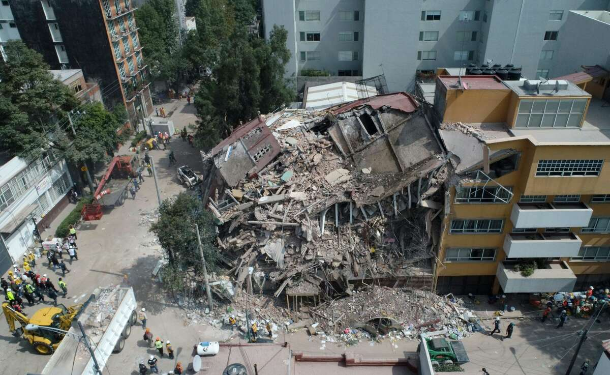 Aerial view of a flattened building in Mexico City taken on September 20, 2017 as the search for survivors continues a day after a strong quake hit central Mexico. A powerful 7.1 earthquake shook Mexico City on Tuesday, causing panic among the megalopolis' 20 million inhabitants on the 32nd anniversary of a devastating 1985 quake.