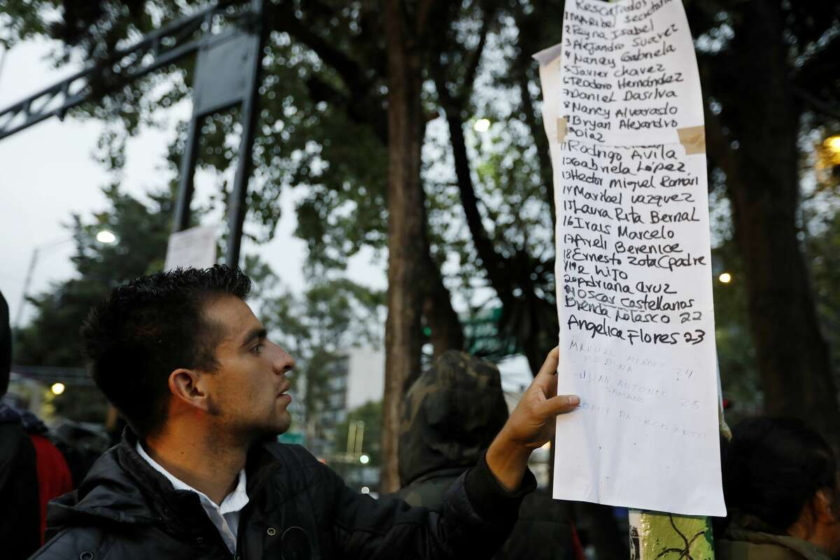 People look for family and friends on a list of people rescued from an office building along Calle Alvaro Obregon in Colonia Condesa, in Mexico City, on Sept. 20, 2017. A powerful 7.1 earthquake rocked central Mexico on Tuesday, collapsing homes and bridges across hundreds of miles, killing at least 225 people.