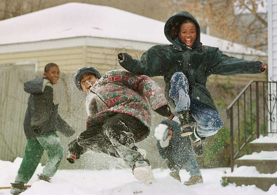 FRIDAY, NOV. 14, 1997 -- Ashley Galloway, 10, and Moneeka Fallen, 11, enjoy the area's first snowstorm of the season on Third Street in Albany. (TIMES UNION PHOTO BY LUANNE M. FERRIS) Photo: LUANNE M. FERRIS, DG / TIMES UNION
