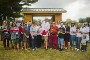 Kurt Faust, center, who spearheaded the Midland Fresh project, cuts a ribbon alongside partners in the mobile farm stand project during a ribbon cutting on Wednesday at Midland Nazarene. (Katy Kildee/kkildee@mdn.net)
